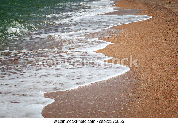 Waves rolling to the sandy beach - csp22375055