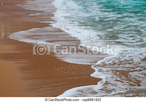 Waves rolling to the sandy beach - csp9991423
