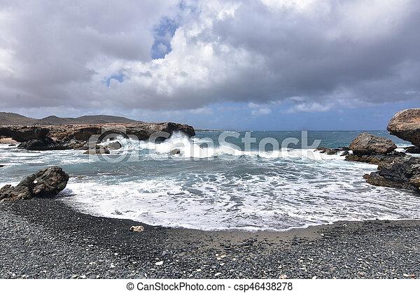 Waves Splashing on to Lava Rocks on Aruba's Black Sand Beach - csp46438278