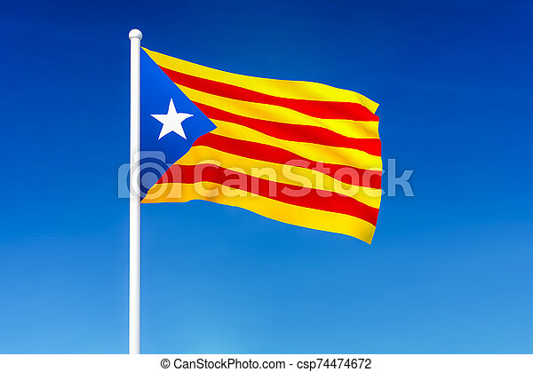 Waving flag of Catalonia on the blue sky background - csp74474672