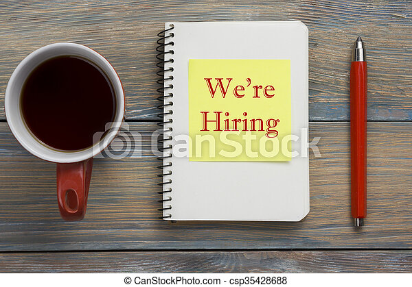 We are Hiring. Office desk table with notepad, pencil and coffe cup. Top view.  - csp35428688