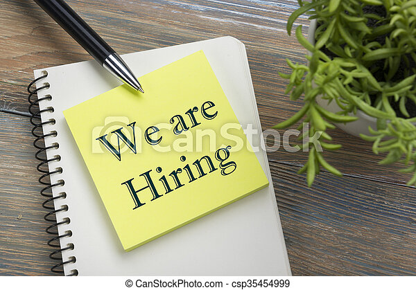 We are Hiring. Office desk table with notepad, pen and flower. Top view.  - csp35454999