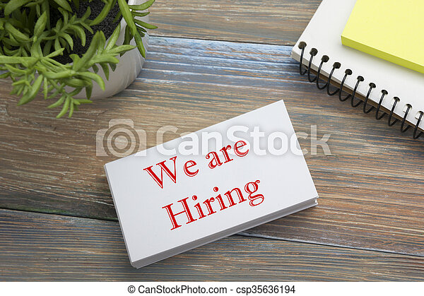 We are Hiring. Office desk table with business card, pen and flower. Top view.  - csp35636194