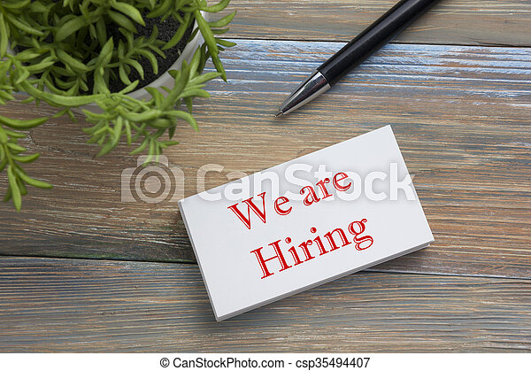 We are Hiring. Office desk table with business card, pen and flower. Top view.  - csp35494407
