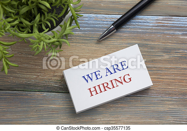 We are Hiring. Office desk table with business card, pen and flower. Top view.  - csp35577135