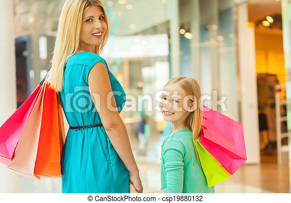 We love shopping together! Cheerful blond hair mother and daughter holding shopping bags and looking over shoulder while standing in shopping mall - csp19880132