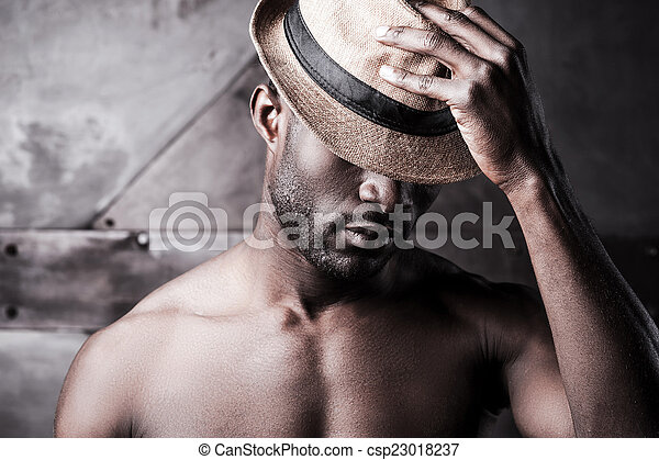 Wearing his favorite hat. Portrait of young shirtless African man adjusting his hat while standing against metal background - csp23018237