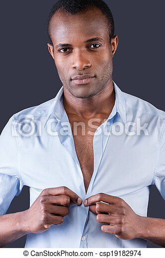 Wearing his favorite shirt. Handsome young black man dressing up his shirt and smiling at camera while standing against grey background - csp19182974