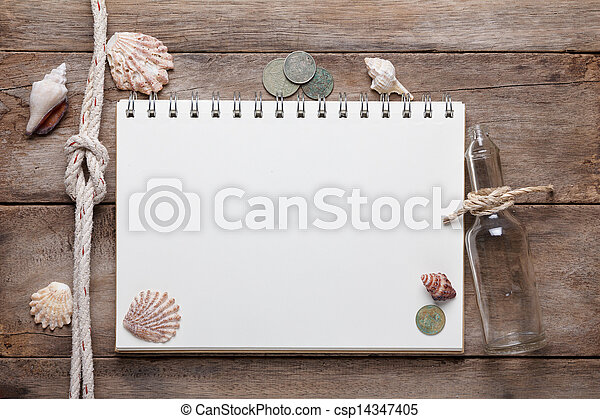 Weathered wooden table with blank notepad, coins and shells - csp14347405