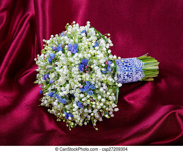 Wedding bouquet from lilies of the valley on a red fabric - csp27209304