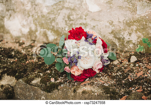 wedding bouquet of the bride on a stone wall background - csp73247558