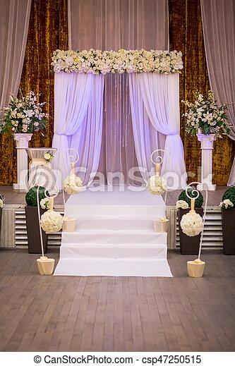 Wedding ceremony hall ready for guests,Luxury, elegant wedding reception table arrangement,Indoors wedding reception venue with decor,Beautiful wedding ceremony design decoration elements with arch - csp47250515
