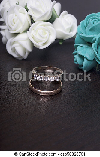 Wedding Decor Wedding Rings Lie On Dark Surface Near Bouquets Of Artificial Flowers