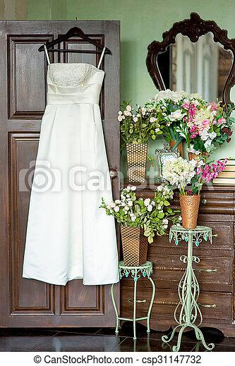 The wedding dress on a hanger hangs on a door near an ancient ...