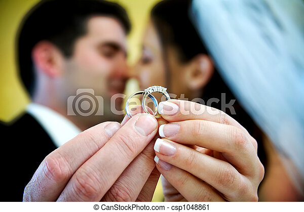The bride and groom are holding up the wedding rings and stock