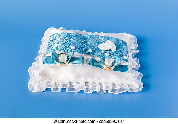 Wedding Rings On A Satin Blue White Pillow On A Blue Background Wedding Rings On A Satin Cushion On A Blue Background