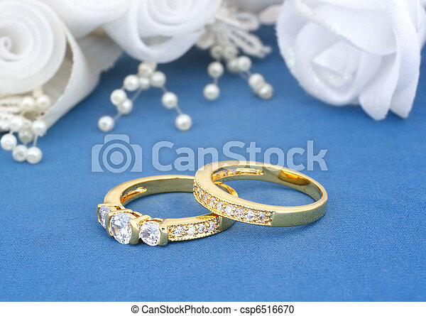 Wedding rings on blue with flowers background stock photography