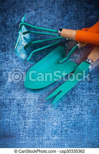 Weeding scoop hand shovel rake hoe on scratched metallic backgro - csp30335362