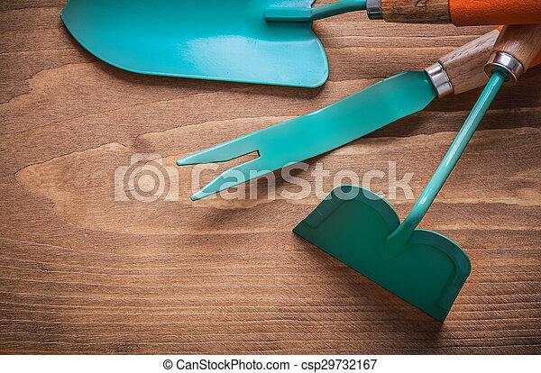 Weeding scoop hand spade hoe on wood board gardening concept - csp29732167