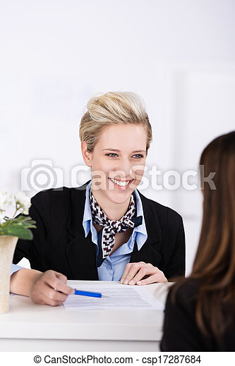 Welcoming hotel receptionist smiling at a guest - csp17287684