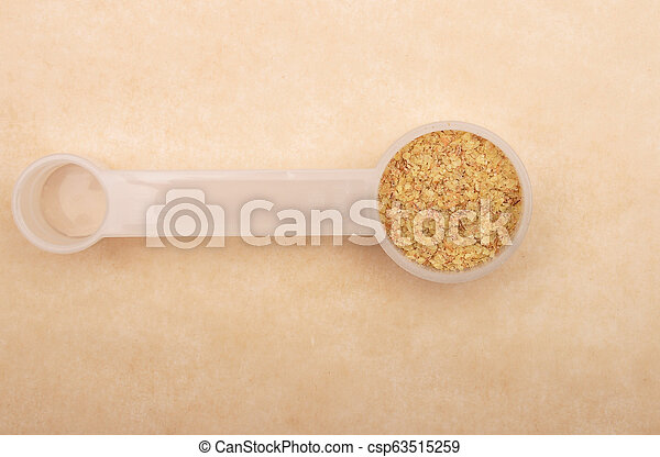 Wheat germs in measuring spoon on brown background - csp63515259