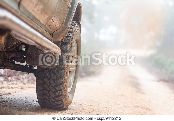 Wheel closeup in a countryside landscape with a muddy road, Off-road travel on mountain road, Adventure Travel, Rainy Season. - csp59412212