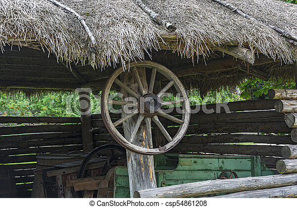 Wheel from the countryside cart hanging on a wooden pole - csp54861208