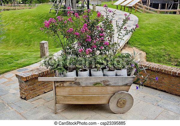 Wheelbarrow full of colorful flowers - csp23395885