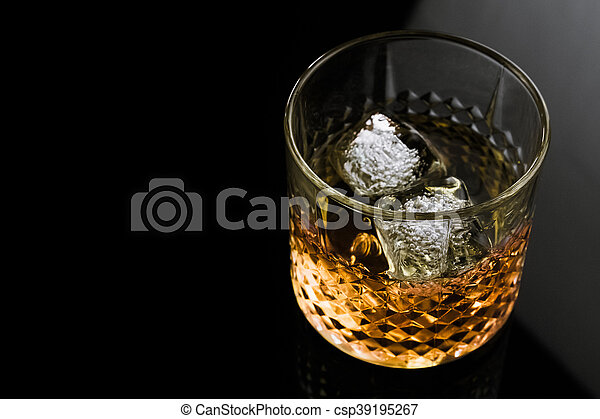 whiskey with ice cubes in glass on black background - csp39195267