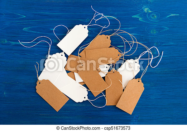 White and brown blank paper price tags or labels set on the blue wooden background, top view. - csp51673573