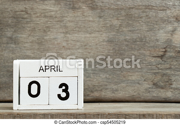 White block calendar present date 3 and month April on wood background - csp54505219