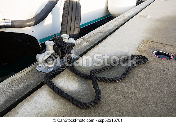 White boat tied to the pier with a black rope - csp52316761