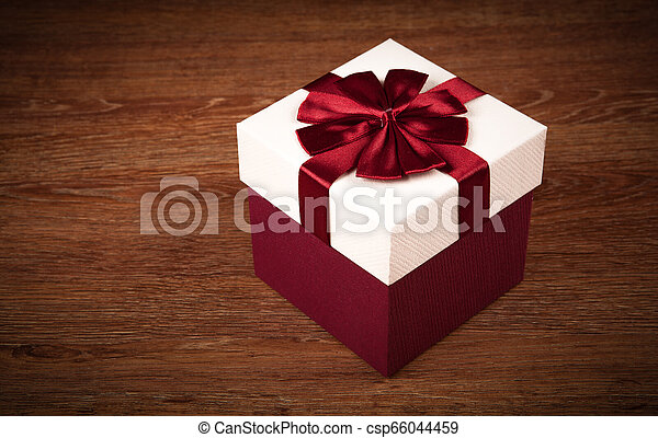 white box with red bow on a wooden background - csp66044459
