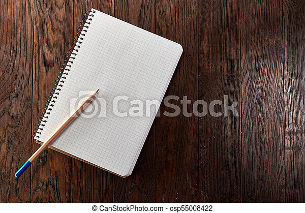 White checked copybook with pencil on pine brown wooden board - csp55008422