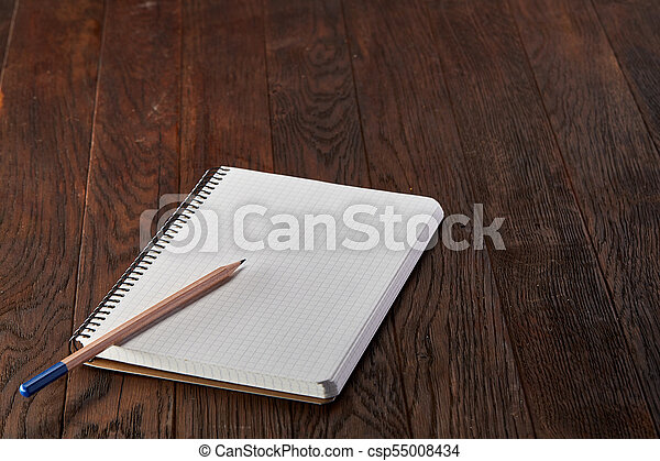 White checked copybook with pencil on pine brown wooden board - csp55008434