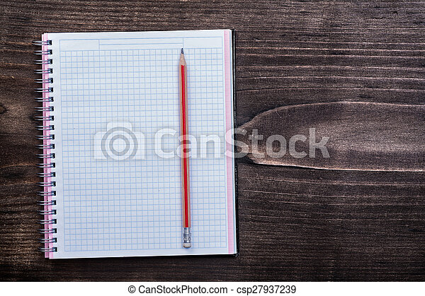 White checked copybook with red pencil on pine brown wooden boar - csp27937239