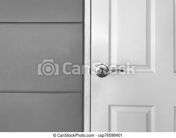 White close wooden door and gray wall, black and white tone - csp76598401