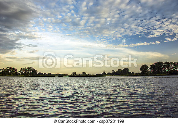 White clouds in the sky over a calm lake - csp87281199