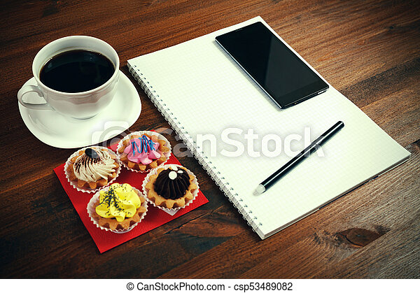White coffee cup with notebook, four cupcakes, smartphone and pen on a wooden table. - csp53489082