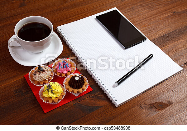 White coffee cup with notebook, four cupcakes, smartphone and pen on a wooden table. - csp53488908