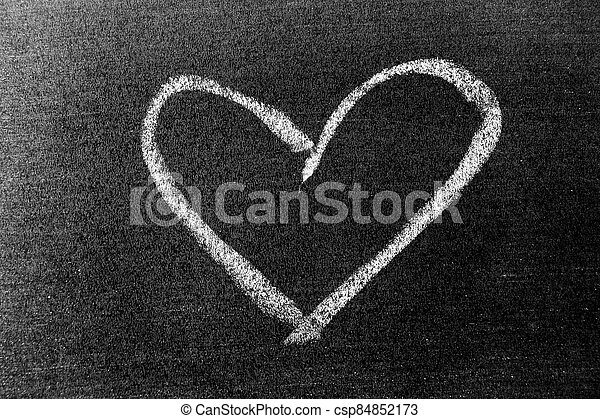 White color chalk hand drawing in heart shape on blackboard background - csp84852173