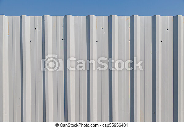 White corrugated metal fence with blue sky