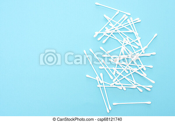 White cotton buds scattered on blue background - csp68121740