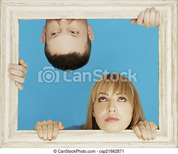 white couple behind wooden frame while man in upside down