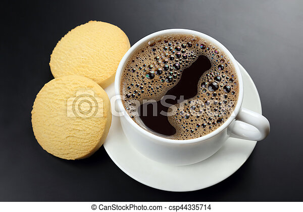 white cup of black coffee with biscuits on a dark background - csp44335714