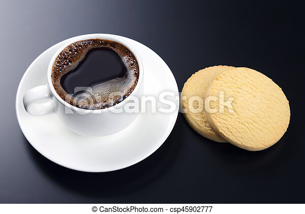white cup of black coffee with biscuits on a dark background - csp45902777