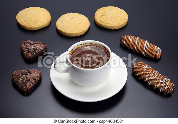 white cup of black coffee with biscuits on a dark background - csp44684581