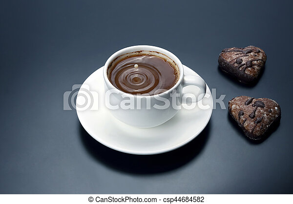 white cup of black coffee with biscuits on a dark background - csp44684582