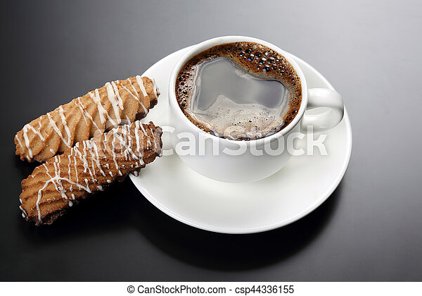 white cup of black coffee with biscuits on a dark background - csp44336155