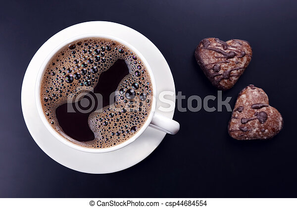 white cup of black coffee with biscuits on a dark background - csp44684554
